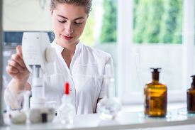 image of chemistry technician  - Young female lab technician doing chemistry experiment - JPG