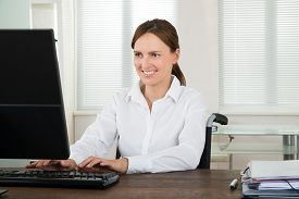 picture of handicapped  - Happy Handicapped Businesswoman Working On Computer In Office - JPG