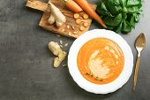 Composition with delicious carrot soup, basil leaves and fresh ginger on table poster