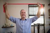 Portrait of smiling senior male patient holding red resistance band at hospital ward poster