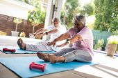 Full length of senior couple doing stretching exercise while sitting on exercise mat in yard poster