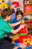 Children building blocks in kindergarten. Couple kids playing toy on floor at home. Girl was embarra poster