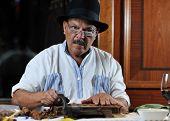 picture of tobaco leaf  - older senior man making luxury handmade cuban cigare - JPG
