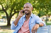 Handsome african man talking on phone at park. Young black man talking on cellphone while sitting on poster