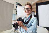 Happy photographer in modern photo-studio poster
