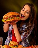 Woman eating hamburger. Student consume fast food. Girl bite of very big burger . Girl trying to eat poster
