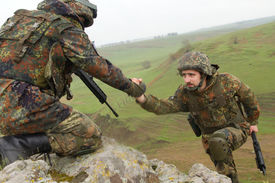 stock photo of army soldier  - Military man helping his friend to climb up the rock - JPG