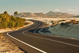 pic of long winding road  - Winding road across the dunes of Corralejo Fuerteventura in the Canary Islands Spain - JPG