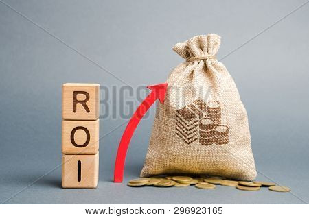 poster of Wooden Blocks With The Word Roi And The Up Arrow With The Money Bag. High Level Of Business Profitab