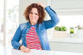 Middle age senior woman with curly hair wearing denim jacket at home confuse and wondering about que poster