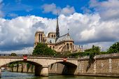 View of bridge over Seine river and famous Notre-Dame cathedral under beautiful sky in Paris, France poster