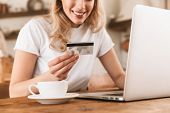 Portrait of smiling blond woman 20s wearing casual t-shirt using laptop and credit card for online s poster