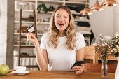Portrait of european blond woman 20s wearing casual t-shirt using smartphone and plastic credit card poster