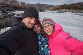 Family selfie at winter journey. Mother, father and son taking selfie photo in forest at beauty sunn poster