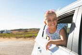 Cute blonde girl in the car looking through window. Smiling little girl having fun travelling by car poster