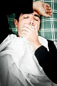 stock photo of young men  - Dramatic desaturated image of a sick man laying in bed and coughing with a handkerchief in his hand - JPG