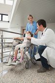 picture of neck brace  - Doctor crouching next to child in wheelchair with neck brace with nurse pushing it - JPG