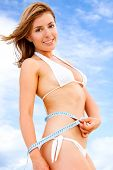 foto of woman bikini  - fit female measuring her waist  - JPG