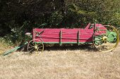stock photo of spreader  - antique manure spreader abandoned along the edge of a field - JPG