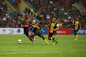 KUALA LUMPUR - AUGUST 10: FC Barcelona's Alexis Sanchez (maroon/blue) leads in attack against Malays