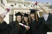 image of convocation  - Portrait of beautiful young students with diplomas standing in front of university - JPG