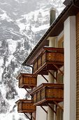 picture of chalet  - Close up on wooden balconies of a chalet at Loeche les bains in winter - JPG