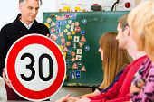 Driving school - driving instructor and student drivers with a tempo thirty Road sign, in the backgr