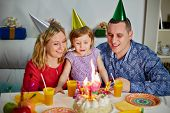 Family of three sits at birthday table, daughter prepares to snuff out candle on cake and parents lo