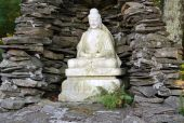 pic of siddhartha  - Marble Buddah statue in a stone grotto with pennies scattered at the base - JPG