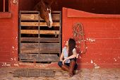 image of horse face  - Young Hispanic woman keeping some company to her horse in a stable - JPG