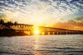 stock photo of florida-orange  - Beautiful colorful sunset or sunrise with broken bridge and cloudy sky - JPG