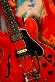 stock photo of fret  - Red electric guitar over textured grunge background - JPG