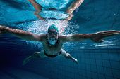 image of breast-stroke  - Fit swimmer training by himself in the swimming pool at the leisure centre - JPG