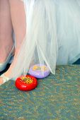 foto of caddy  - Bride holds her wedding dress up to be pinned and hemmed - JPG