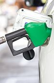 stock photo of fuel economy  - Gas pump nozzle in the fuel tank of a white car - JPG