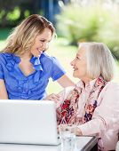 picture of grandmother  - Happy granddaughter and grandmother looking at each other while using laptop on nursing home porch - JPG