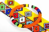 stock photo of zulu  - circular beaded zulu armband atop two wristbands - JPG