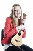 stock photo of ukulele  - teenage girl holds ukulele in studio against white background - JPG