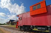 stock photo of caboose  - Bright red vintage caboose parked on railroad tracks near yellow railway depot - JPG