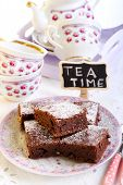 stock photo of brownie  - Chocolate brownies dusted with icing sugar on plate and a sign saying Tea Time - JPG
