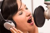 stock photo of studio  - beautiful young brunette girl singing in music studio - JPG