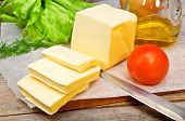 picture of butter-lettuce  - butter on parchment paper with vegetables on a wooden table
