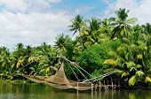 stock photo of alleppey  - Coco trees reflection and chinese fishing nets at back waters of Kerala India - JPG