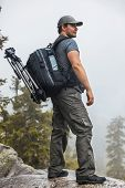 pic of rainy weather  - Young man tourist with backpack and tripod standing on mountain top at rainy weather - JPG