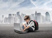 stock photo of school building  - Smiling child sitting in front of a laptop with cityscape on the background - JPG