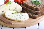 stock photo of collate  - Soft cheese with herbs slices of spicy brown bread on board - JPG