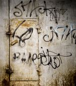 stock photo of spayed  - City street paint in black on grey rusted metal with a locked door in rust - JPG