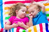 picture of brother sister  - Two kids sleeping in bed under colorful blanket - JPG