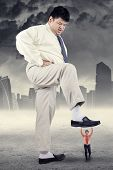 pic of big-foot  - Business competition concept with big businessman treading little entrepreneur - JPG