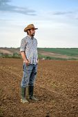 picture of farm land  - Portrait of Adult Male Farmer Standing on Fertile Agricultural Farm Land SoilLooking into Distance - JPG